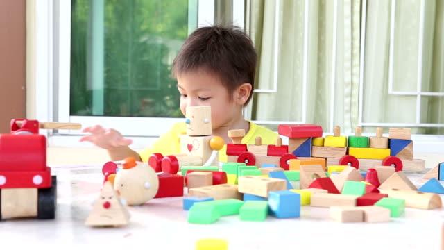 vídeos de stock, filmes e b-roll de criança com brinquedos de madeira - brinquedo