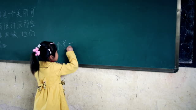 Child writing in Chinese on the blackboard
