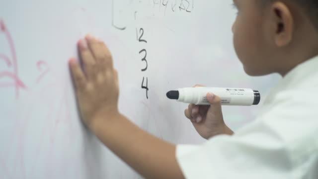vídeos y material grabado en eventos de stock de niños escribiendo matemáticas en una pizarra - adversidad