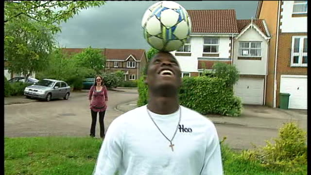vidéos et rushes de foster care fortnight initiative; england: surrey: ext joe playing football in street watched by his foster mother alison cox - famille d'accueil
