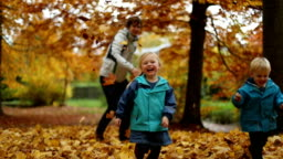 Childhood Moments: Teenager and Children Playing with Autumn Leaves in Park 4
