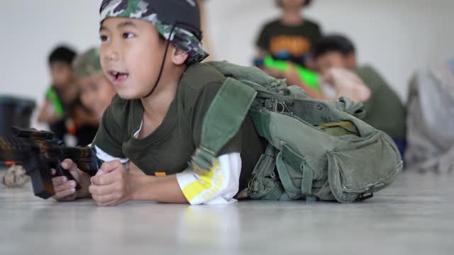 kinderschüler und freunde spielen wie soldat in der schulklasse - militäruniform stock-videos und b-roll-filmmaterial