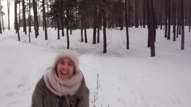 childlike adult happily runs along the path and playing snowballs in the wintry forest - mitten stock videos and b-roll footage