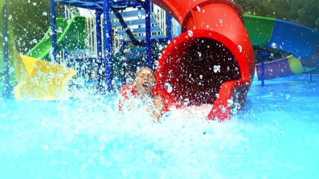 barn-en pojke och en flicka-rida på en vattenrutschbana - utebassäng bildbanksvideor och videomaterial från bakom kulisserna