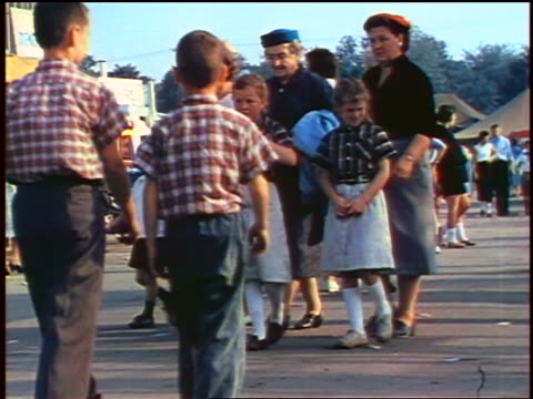 stockvideo's en b-roll-footage met 1957 children + adults walking at carnival / feature - overhemd