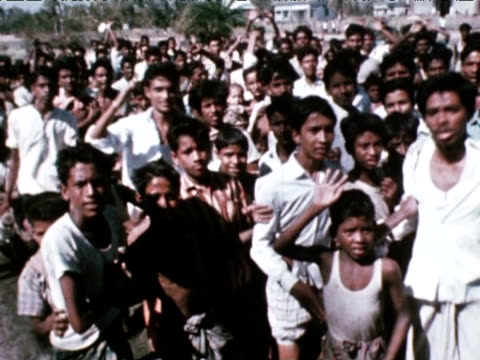 vidéos et rushes de children and adults approach helicopter to queue for food following floods 1970 - est