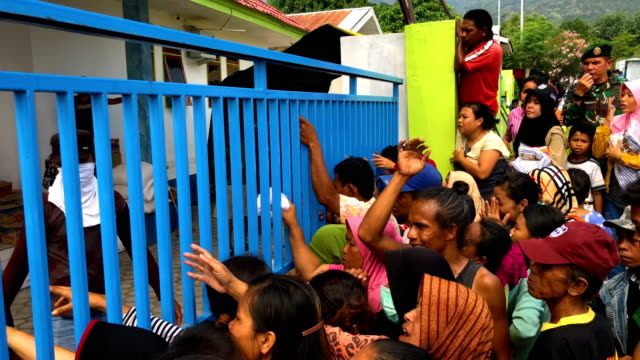 children and adults grab food being distributed by the military after being displaced by an earthquake and tsunami on october 04 2018 in palu... - {{ contactusnotification.cta }}点の映像素材/bロール