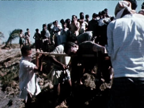 children and adults observe as dead bodies and cattle are carried away and buried following floods 1970 - east stock videos & royalty-free footage