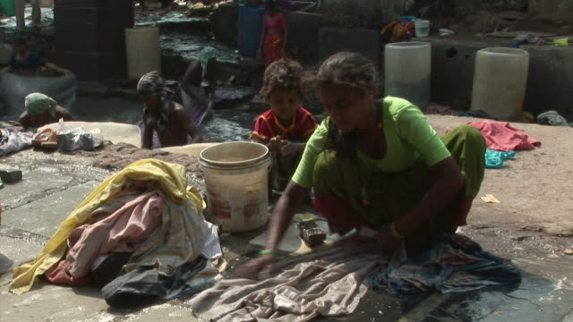 Children and adults washing clothes beside street sewer / Dharavi Mumbai India