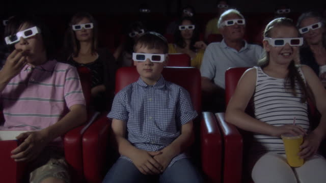 Children and adults watching 3d movie at the movie theater