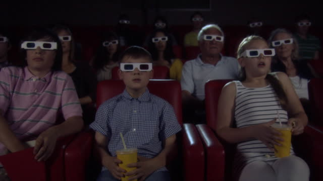 vídeos de stock, filmes e b-roll de children and adults watching 3d movie at the movie theater - óculos de terceira dimensão