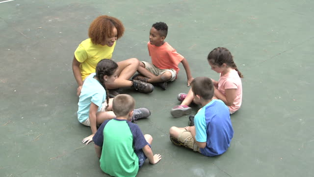 children and camp counselor run up and sit in circle - child sitting cross legged stock videos & royalty-free footage