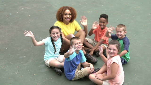 children and camp counselor waving at camera - summer camp helper stock videos & royalty-free footage