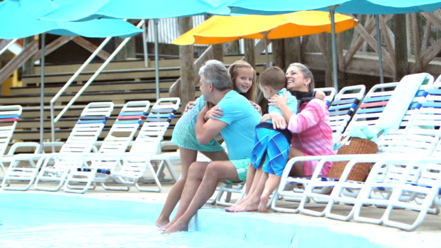 Children and grandparents hugging poolside