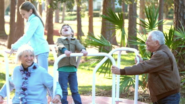 barn och mor-och farföräldrar på lekplats karusell - flergenerationsfamilj bildbanksvideor och videomaterial från bakom kulisserna