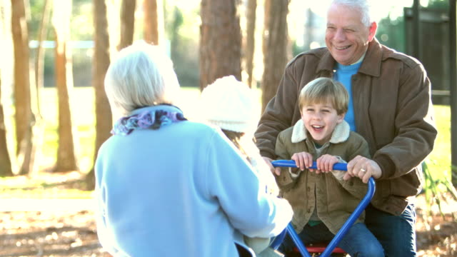 children and grandparents playing on teeter totter - multi generation family stock videos & royalty-free footage