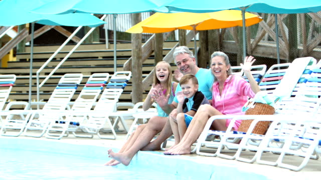 children and grandparents sitting poolside, waving - 50 59 years video stock e b–roll