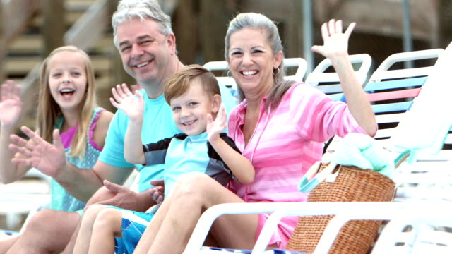 Children and grandparents sitting poolside, waving