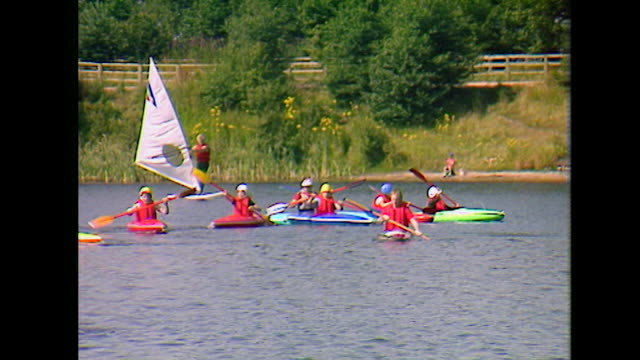 ws children and instructor kayaking on uk lake; 1984 - life jacket stock videos & royalty-free footage