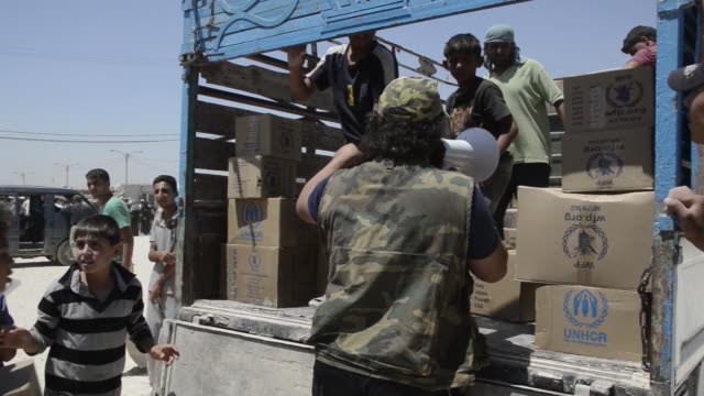 children and men load aid boxes onto truck at syrian civil war refugee camp in jordan - シリア難民問題点の映像素材/bロール