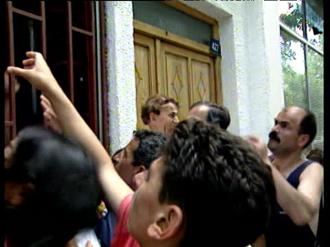 Children and people scramble for bread outside barred window of shop Kosovo 21 Jun 99