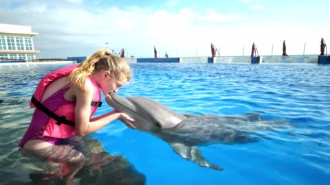 stockvideo's en b-roll-footage met kinderen en trainer in water, meisjes kussen dolfijn - dolfijn