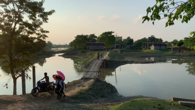 children and villagers crossing a bamboo-made bridge over water body in a village in barpeta district of assam. - backgrounds stock videos & royalty-free footage