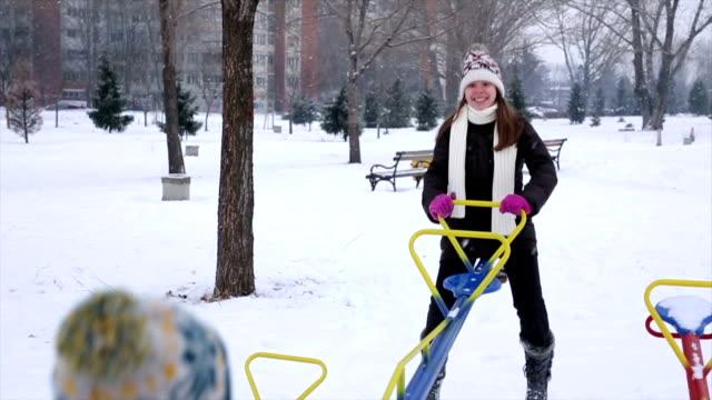 vídeos y material grabado en eventos de stock de niños divirtiéndose en el parque de invierno - balancín