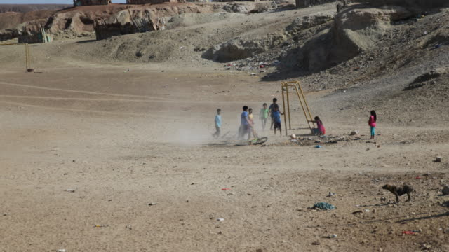 Children are playing football in a dry and sandy area in a very poor area in Tortuga Peru