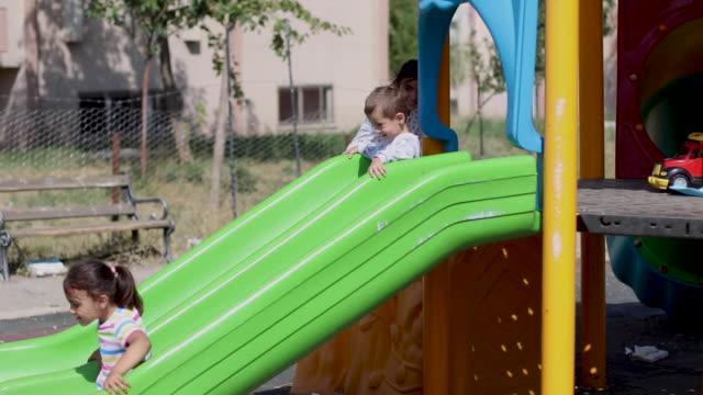 vídeos y material grabado en eventos de stock de los niños están jugando en el patio de recreo - estructura metálica para niños