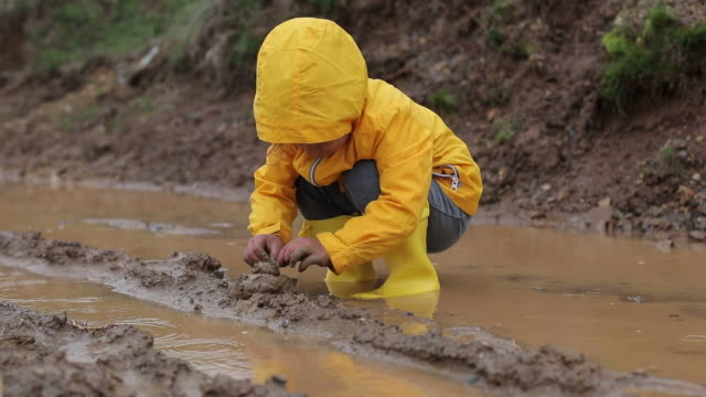 children are playing with mud in muddy water - raindrop stock videos & royalty-free footage