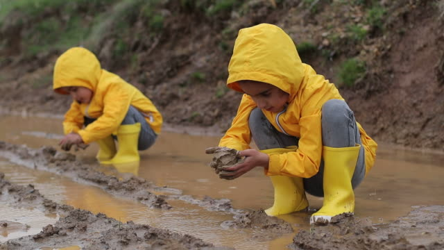 children are playing with mud in muddy water - mud stock videos & royalty-free footage