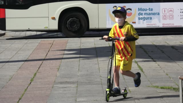 children are seen on the streets on the first day as the government eases the lockdown rules on april 26, 2020 in barcelona, spain. starting last... - non urban scene stock-videos und b-roll-filmmaterial