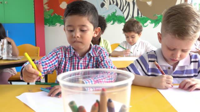 Kinderen op de basisschool schilderen en plezier