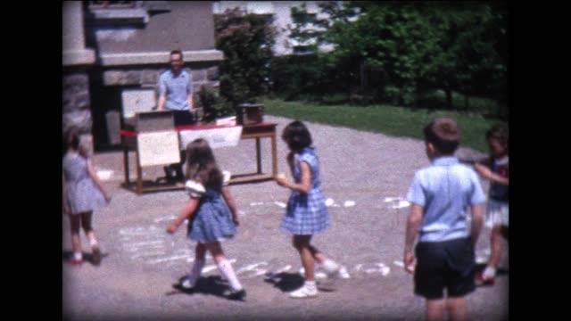 vídeos de stock, filmes e b-roll de 1966 children at school fair playing cake walk - mischief