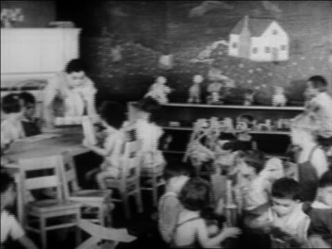 vídeos de stock e filmes b-roll de pan children at tables being served snack in nursery school / wpa project / newsreel - professora
