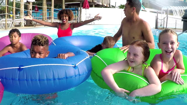 Children at water park on lazy river with camp counselors