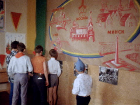 vidéos et rushes de children attend young pioneer camps during olympics; children looking at pennants and posters map of great britain painted and drawn by the children - banderole signalisation