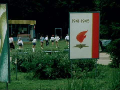 children attend young pioneer camps during olympics; young pioneers boys playing football patriotic posters displayed around the camp hut with... - former soviet union stock videos & royalty-free footage