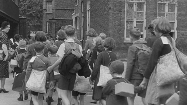 1939 MONTAGE Children being evacuated to the country from the city, walking with guardians in a long line, carrying bags and suitcases, during World War II / United Kingdom