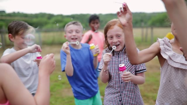 children blowing bubbles - playful stock videos & royalty-free footage