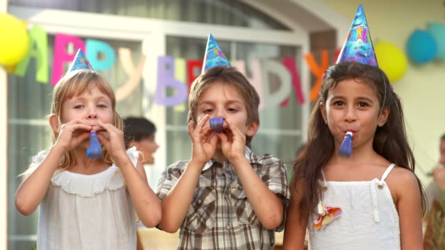hd: children blowing party horn blowers - birthday stock videos & royalty-free footage