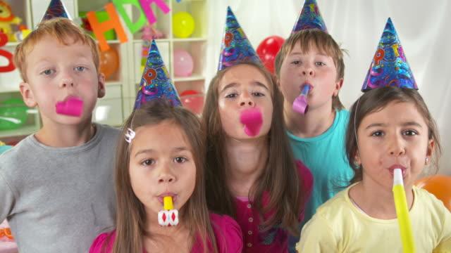 vídeos de stock, filmes e b-roll de hd: grupo de crianças balançando horn blowers - birthday
