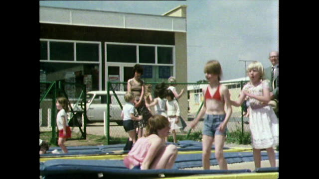 vídeos y material grabado en eventos de stock de children bounce on trampoline at uk holiday resort; 1981 - pantalón corto