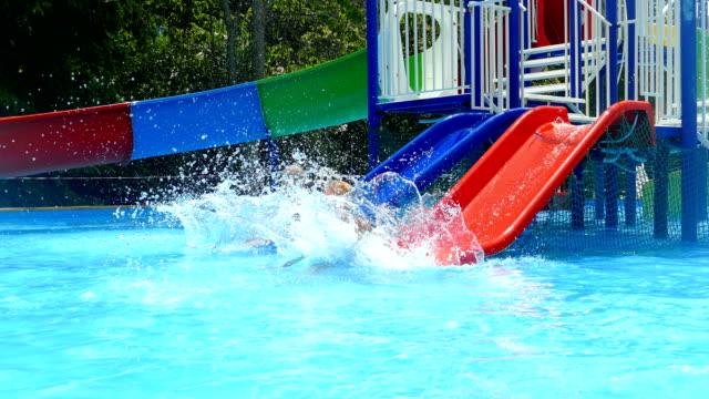 barn-pojke och flicka-ha kul på en vattenrutschbana - utebassäng bildbanksvideor och videomaterial från bakom kulisserna