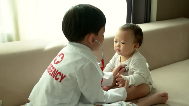 children boy playing doctor with his baby in playroom or kindergarten. - test drive stock videos & royalty-free footage