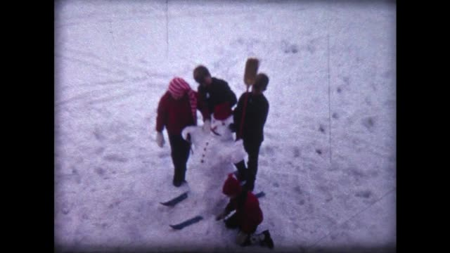 1966 children build snow man on skis - snowman stock videos & royalty-free footage