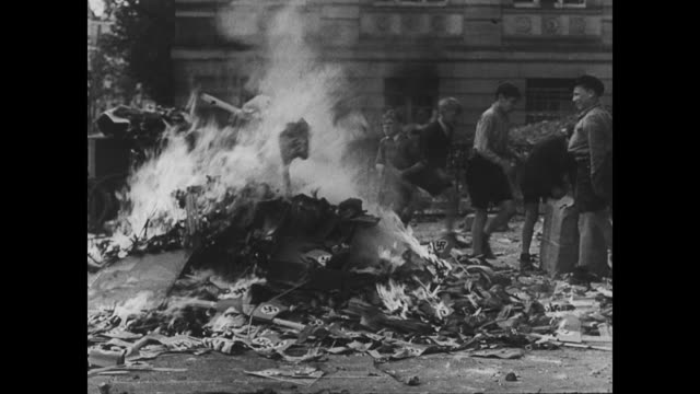 / children burning symbols of the nazis in the post war german streets / fire keeps burning as boys find more and more fuel children burn nazi... - 1945 stock-videos und b-roll-filmmaterial