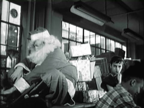 montage children busily packing presents into boxes and dressed-up santa writing japan on stacked boxes / new york city, new york, united states - anno 1950 video stock e b–roll