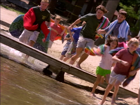CANTED children + camp counselors with towels running on side of lake + jumping over dock